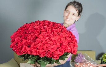 Florist woman prepares a big bouquet of red roses. One hundred and one dutch rose. Florist flower shop. Holland. Wrapping paper. Concept holiday, birthday, World Women's Day, 8 March