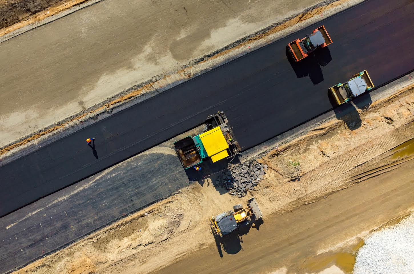Aerial view on the road rollers working on the new road construction site
