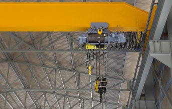 Close up of an indoor factory overhead crane on a yellow beam