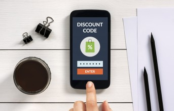 Discount code concept on smart phone screen with office objects on white wooden table. All screen content is designed by me.