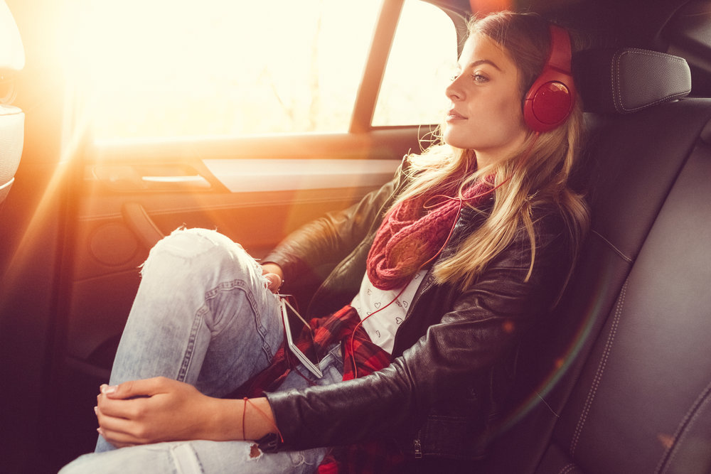 Woman travelling at the back seat of a car and listening to the music from mp3 player