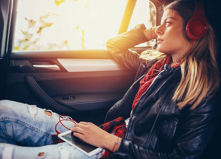 Young-woman-looking-out-window-listening-to-music
