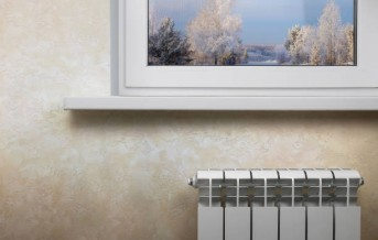 White sectional heating radiator under a white window. The image has an empty space for the inscription.