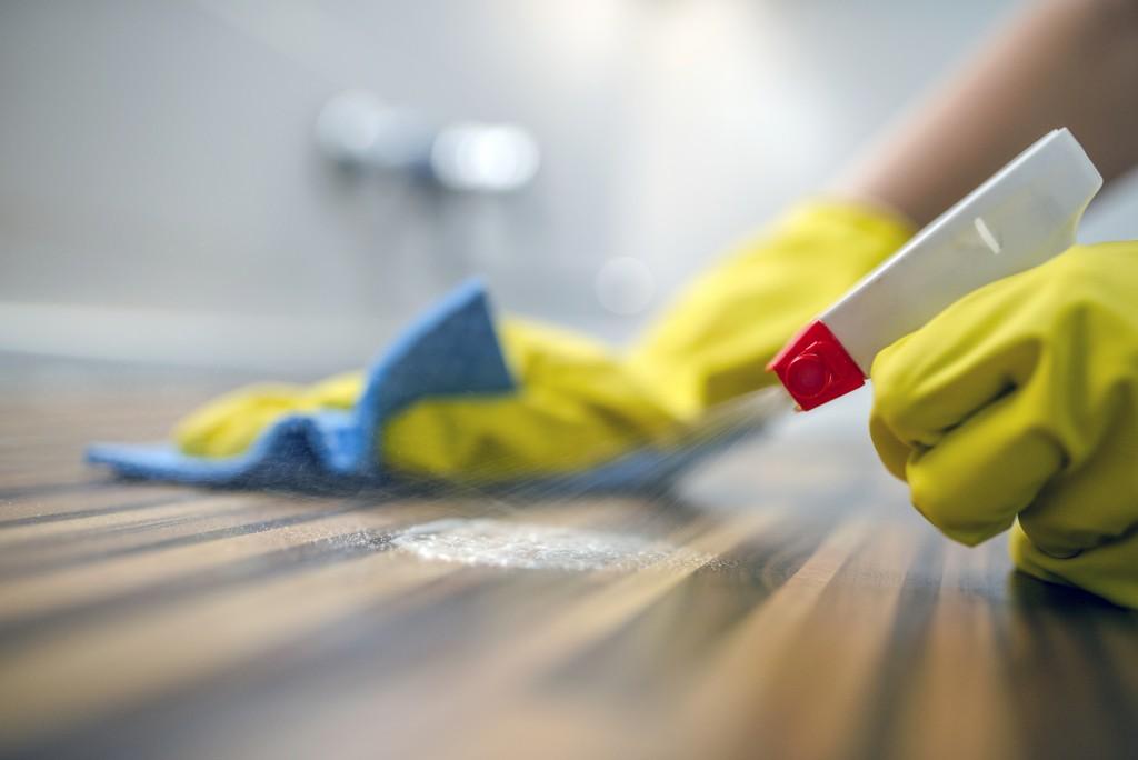 Photo of Woman or man cleaning kitchen cabinets with sponge and spray cleaner. Female or male hands Using Spray Cleaner On Wooden Surface. Maid wiping dust while cleaning her house wearing yellow protective gloves, close-up