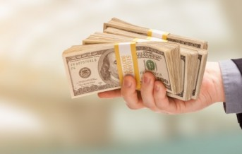 Male Hand Holding Stack of Cash Wide Banner With Room For Copy.