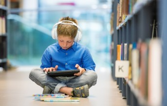 Schoolboy with headphones and digital tablet sitting on the floor in library.