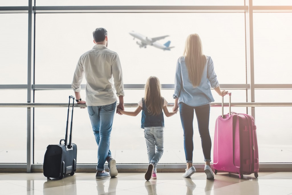 Family in airport. Attractive young woman, handsome man and their cute little daughter are ready for traveling! Happy family concept.
