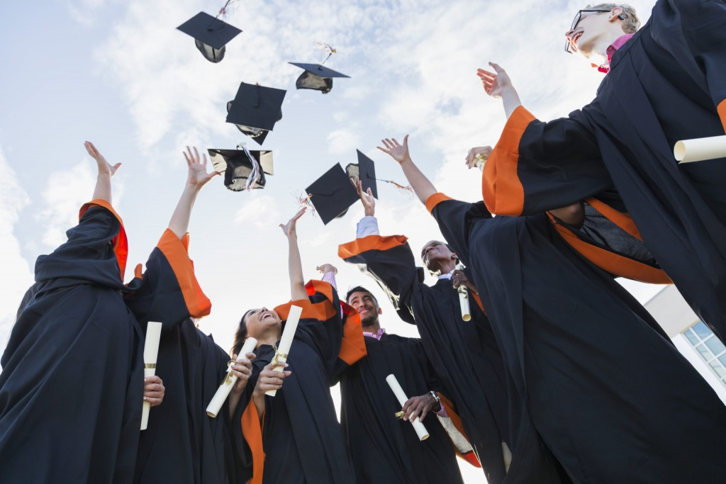 A group of seven multi-ethnic high school or university graduates wearing graduation gowns, holding diplomas. Throwing their caps in the air.