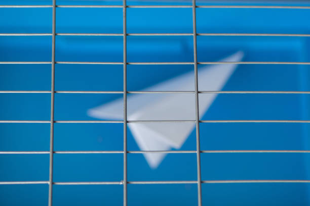Russia blocks Telegram: paper plane behind bars on a blue background