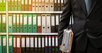 businessman holding data files on binder shelves background
