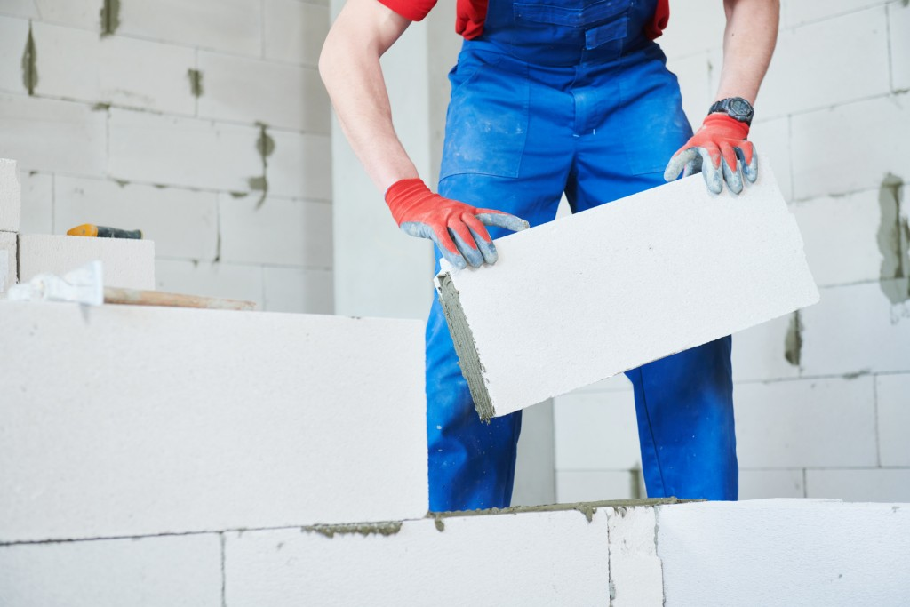 Bricklaying construction work or walling. bricklayer builder working with autoclaved aerated concrete blocks. slow motion
