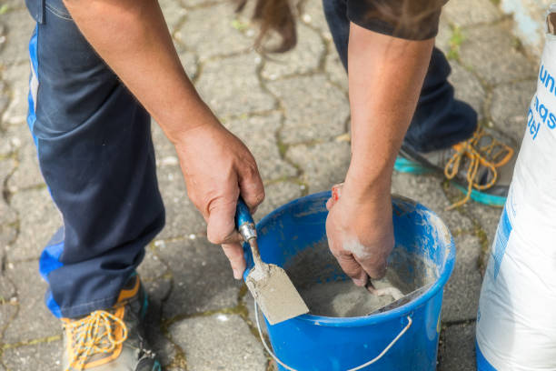Two hands with bricklayer trowel, do prepare mortar.