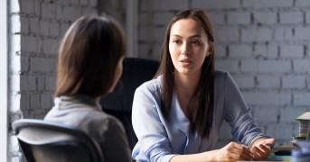 Serious professional female advisor consulting client at meeting talking having business conversation or making offer, insurer giving advice, mentor teaching intern, hr speaking at job interview