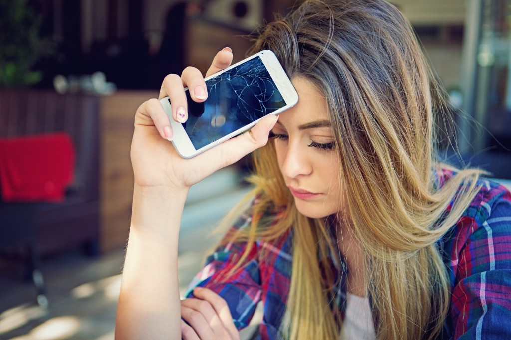 Young girl is devastated after her mobile phone is fall down.