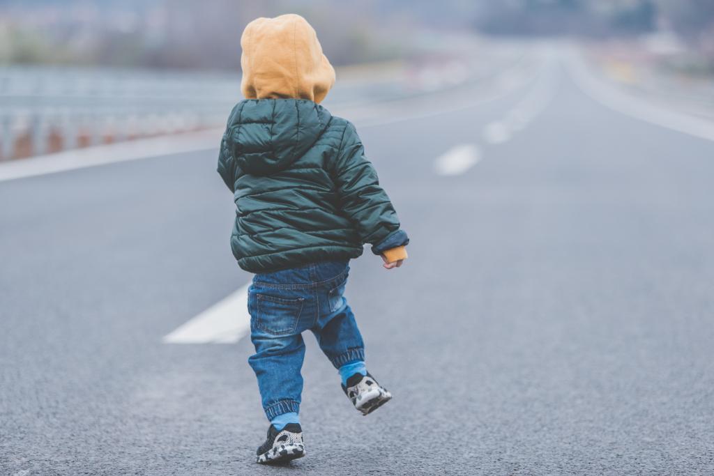Little boy running away on an empty high way road