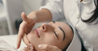 Beauty, spa and cosmetology concept. Young woman lies with closed eyes, cosmetologist making procedure for facial skin rejuvenation, facial massage.