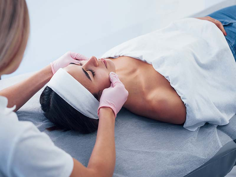 Close up view of woman that lying down in spa salon and have face cleaning procedure by cosmetologist in gloves.